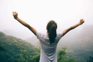 Happy teen with outstretched arms enjoying the view on morning mountain valley because she has finished adolescent therapy